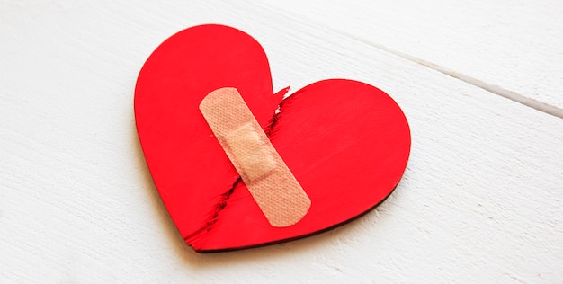 Two parts of red broken wooden heart taped by a patch.