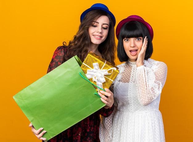 Due ragazze da festa che indossano un cappello da festa sono contente di aver tirato fuori il pacchetto regalo dal sacchetto di carta guardandolo eccitato un'altra ragazza che tiene la mano sul viso isolata sul muro arancione