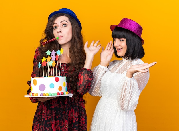 Two party women wearing party hats and holding cake with stars
