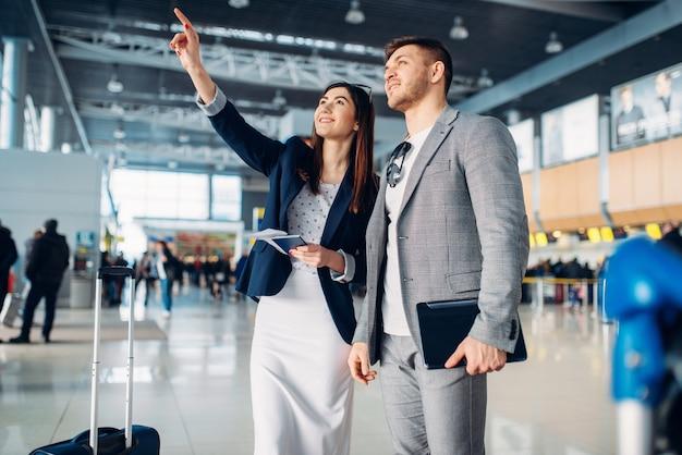 ビジネスクラスの2人の乗客が空港で待っている、出張。ビジネスマンやエアターミナルのビジネスウーマン