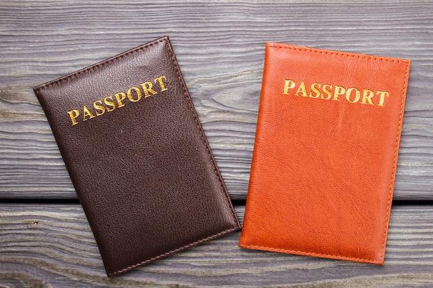 나무에 두 개의 여권. 책상에 갈색과 빨간색 여권.