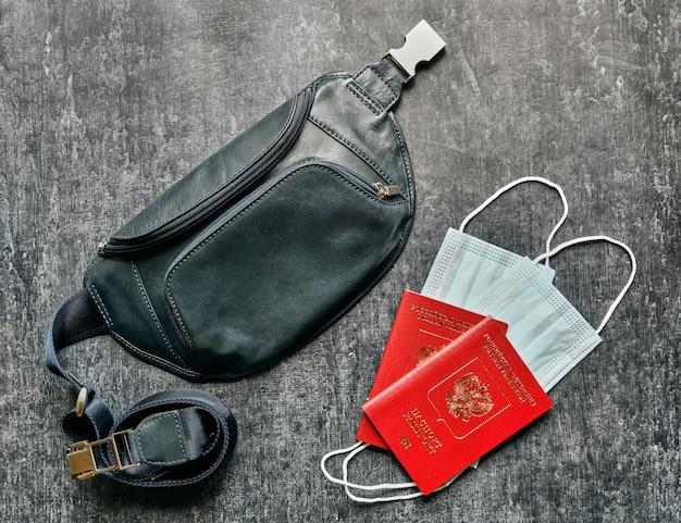 Два паспорта, защитные маски и кожаная дорожная поясная сумка, концепция путешествий по пандемии