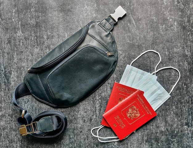 Two passports, protective masks and leather travel belt bag, pandemic travel concept