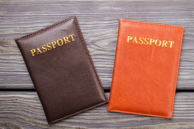 Two passports on wood. brown and red passport on the desk.
