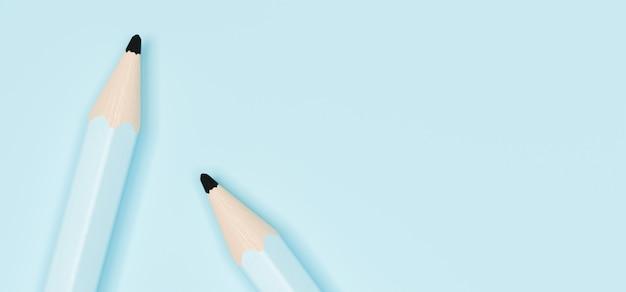 Два пастельных синих деревянных карандаша на синем