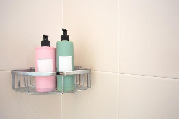 タイル張りの壁にシャワーラックの2つのパステルカラーの石鹸ディスペンサー
