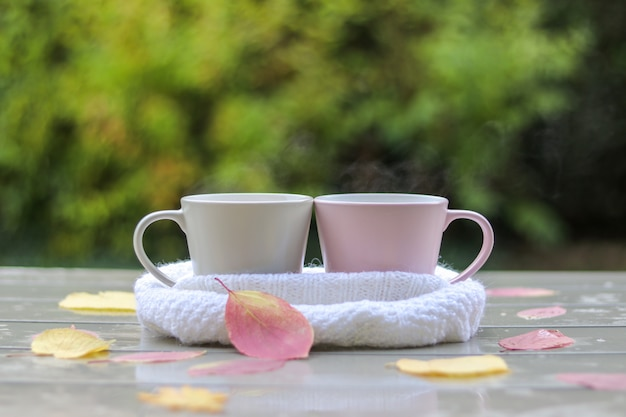 Two pastel cups with hot tea in white knitted scarf on wet table