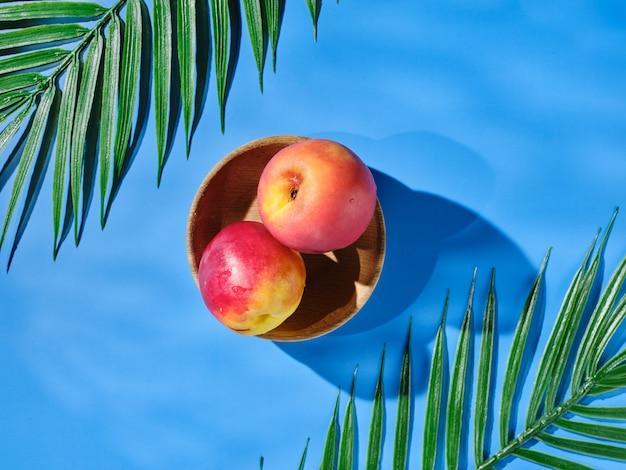 Два персика в миске на столе - вид сверху