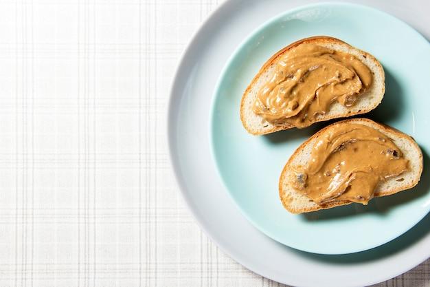 두 개의 땅콩 버터 샌드위치가 파란색 접시에 있습니다.
