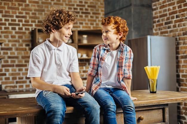 포드에 두 개의 완두콩. 밤나무 머리 소년 스마트 폰 및 이어폰으로 웃고 부엌에서 험담하는 동안 그의 빨간 머리 동생을보고.