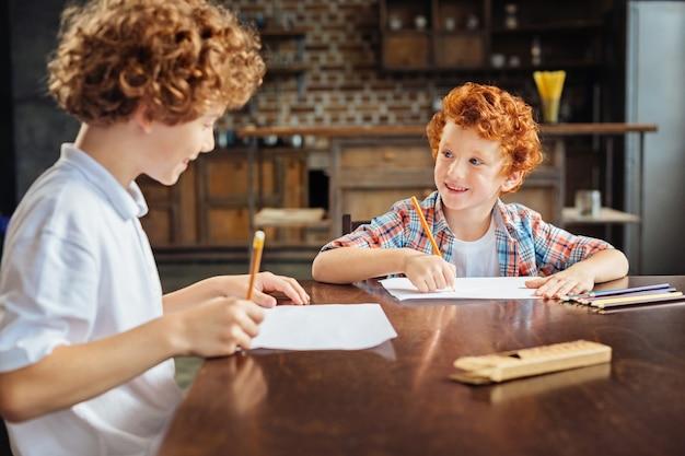Две горошины в стручке. селективный фокус на счастливом рыжем мальчике, смотрящем на своего старшего брата с взволнованной улыбкой на лице, когда оба вместе проводят свободное время и рисуют.