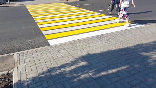 横断歩道、生命の安全、輸送の概念の新しい黄白色のマーキングで道路を横断する2人の歩行者。