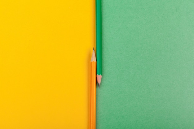 Two pencils lie at the junction of two colored papers green and yellow top view