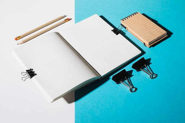 Two pencils; open notebook attach with bulldog clip and spiral notepad