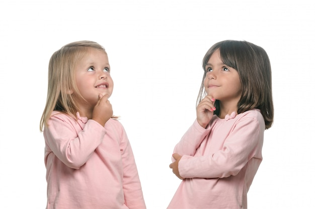 Two pensive little girls thinking about something