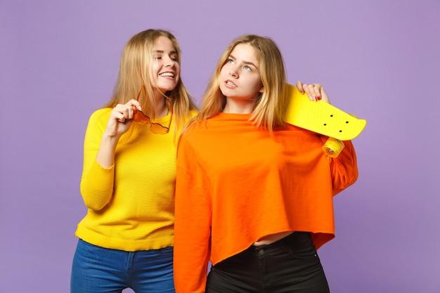 鮮やかな服を着た2人の物思いにふける若い金髪の双子の姉妹の女の子、ハートの眼鏡はパステルバイオレットブルーの壁に分離された黄色のスケートボードを保持します。人々の家族のライフスタイルの概念。