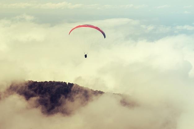 Два человека летят на параплане в небе. тонированный. тандемный полет