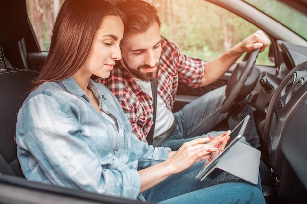 Two people are sitting together in car and looking on tablet that girl is holding. they are looking at the screen with interest and excitement.