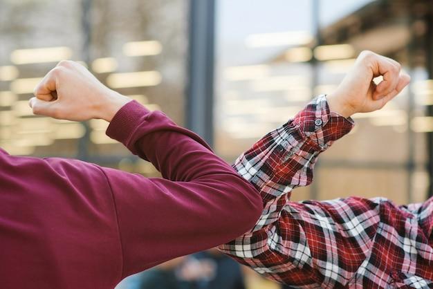 Two people bump elbows to avoid coronavirus outdoors.