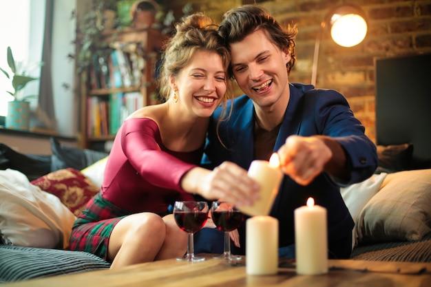 집에서 함께 축하하는 두 사람. 그들은 테이블에 촛불을 밝히고 있습니다