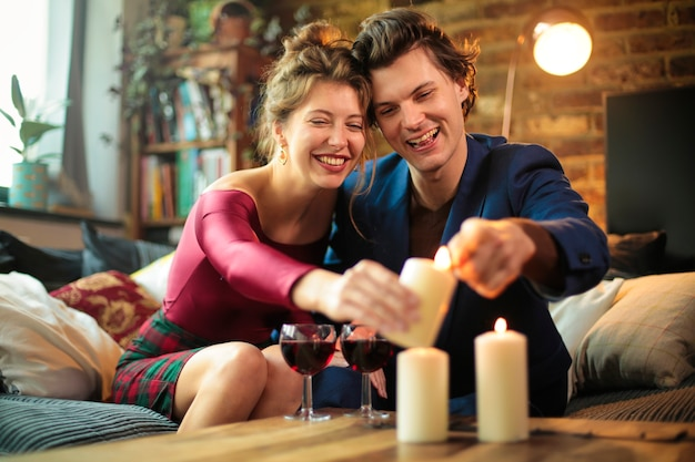 Two people celebrating at home together. they are lighting up candles on the table