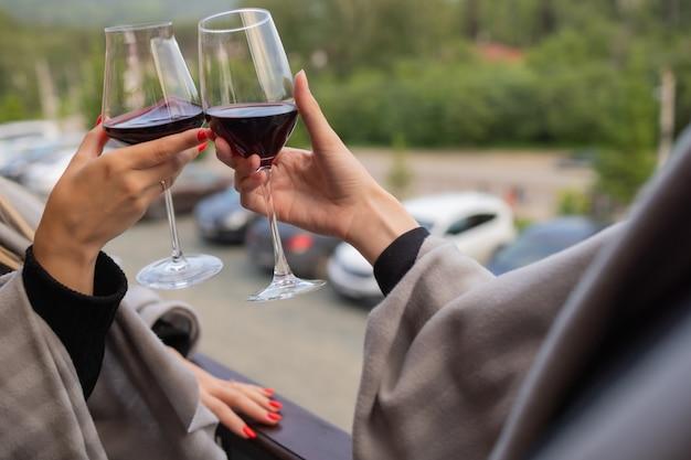 Два человека звенят бокалами с красным вином, празднуют успех или произносят тост в винном ресторане, у стойки с винными бутылками, крупным планом.