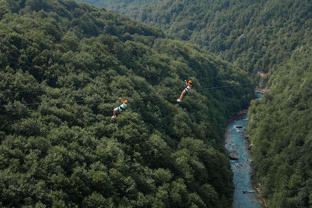 緑の森を背景にジップラインを降りる二人