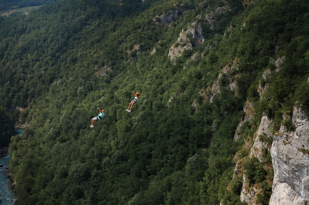 Two people descend on the zip line against the backdrop of green hills