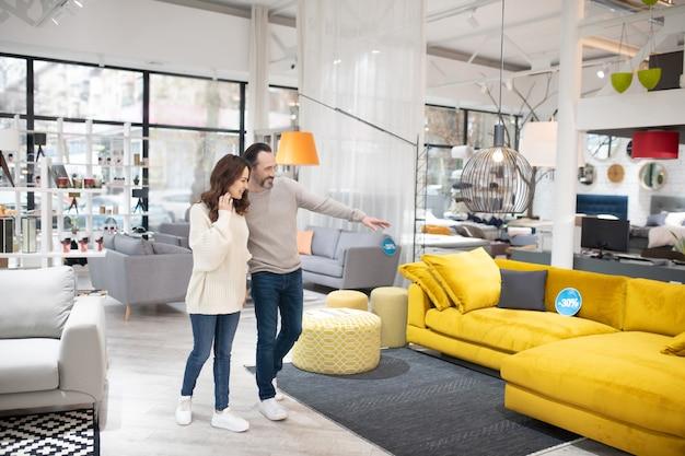 Два человека обсуждают модели мебели в современном мебельном магазине