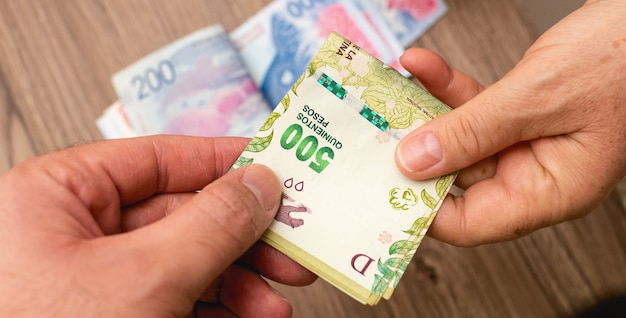 Two people doing business with money bills from argertina in close up photo