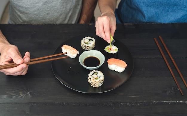 초밥을 먹는 두 사람. 음식 개념.