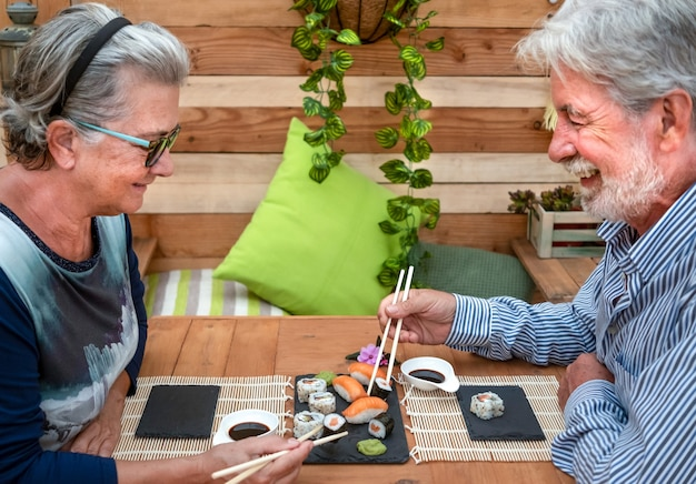 Two people eating sushi at home. senior man and woman smiling, holding chopsticks. wooden table