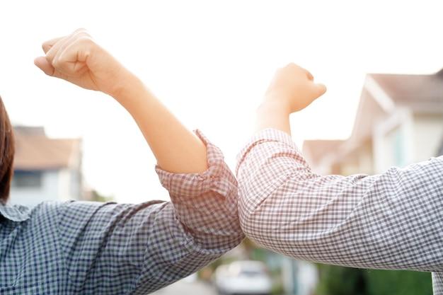 Два человека удар локтем. новое нормальное приветствие, чтобы избежать распространения вируса короны. деловой человек встречается голыми руками, социальное дистанцирование. никаких объятий или рукопожатий. остановить вспышку.