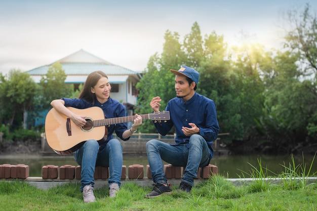 二人の友人は休日に幸せな夏にギターの休息をします