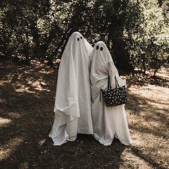 Two people in ghost costumes hugging each other in forest