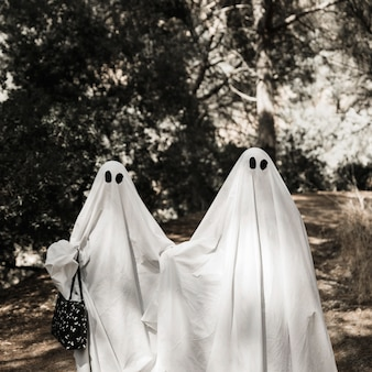 Two people in ghost costumes walking in forest