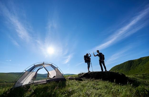 두 사람이 산속 캠핑 근처에서 서로에게 하이 파이브를 주다