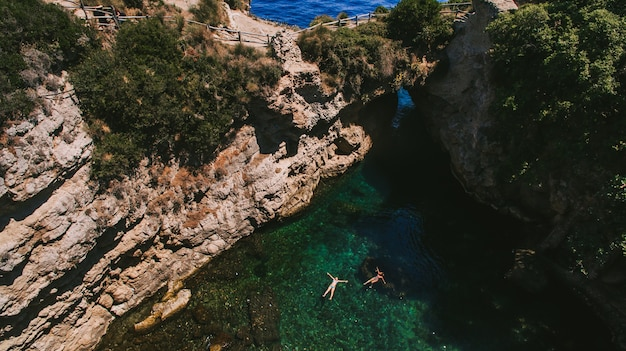 Two people in green bay in capri island italy inside cave view