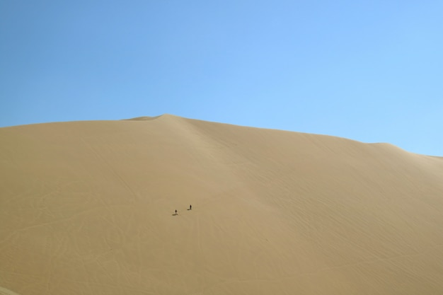 Two people having fun on the vast sand dune of huacachina desert, ica region, peru, south america