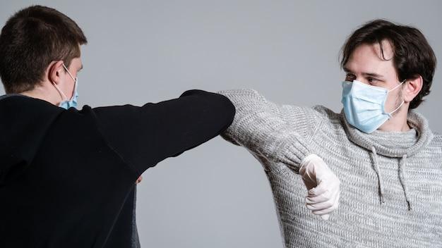 コロナウイルスを避けるために二人が肘を打った