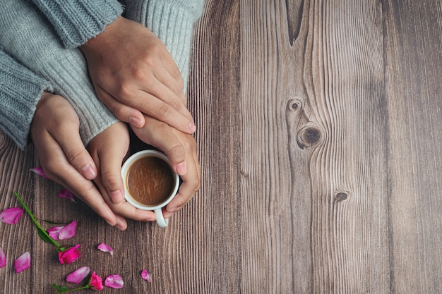 Two people holding cup of coffee in hands with love and warmth on wooden table