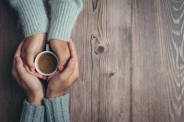 나무 테이블에 사랑과 따뜻함으로 손에 커피 한잔 들고 두 사람