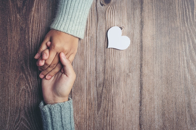 Two people holding hands together with love and warmth on wooden table