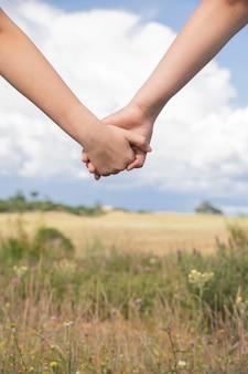 Due persone che si tengono per mano insieme: amicizia, amore concetti