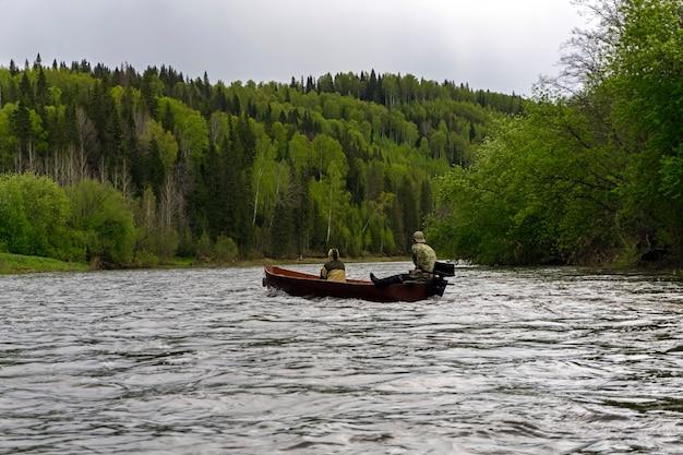 船外機を備えた伝統的な木製の平底ボートに乗った2人が川に沿って浮かんでいます