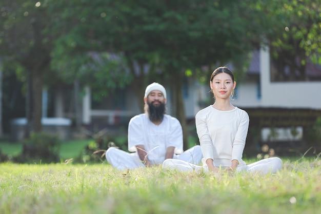 자연 속에서 요가 하 고 흰 옷을 입은 두 사람