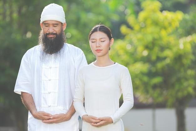 자연 속에서 명상하는 흰 옷을 입은 두 사람