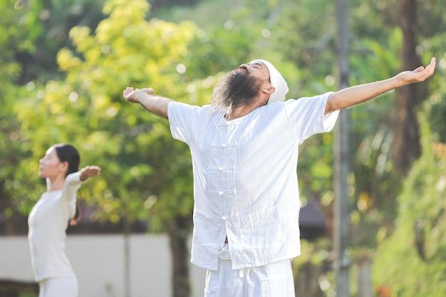 Два человека в белом костюме медитируют на природе