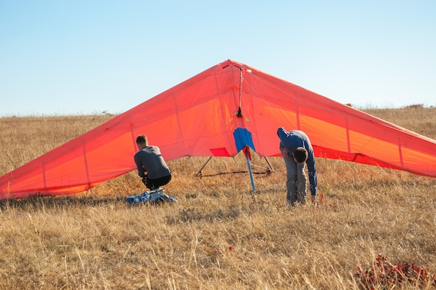 Two people launch the paraglider