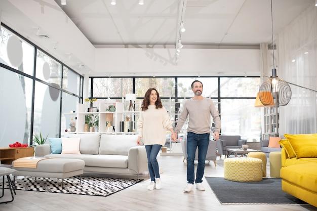 Два человека смотрят на модели мебели в магазине современной мебели